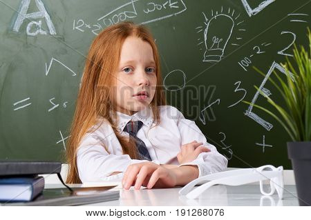 Schoolgirl sitting at the table, on the table glasses, schoolgirl on the background of the school board.