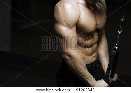 Cropped shot of male fitness model working out on simulator machine. Male bodybuilder with strong perfect body posing in gym.