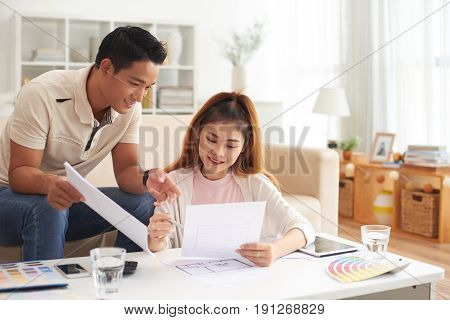 Portrait of young Asian family discussing interior design smiling while planning new house