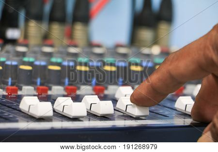 hand on a sound mixer control equipment old which has dust. select focus with shallow depth of field.