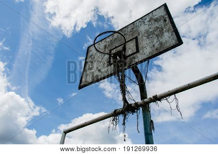 Old Basketball Court, Basket, Snatched Netting Against The Sky