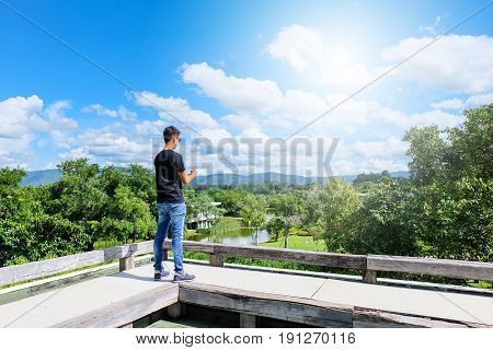 Male tourists are taking notes on the trip on a landscape with a bright sky