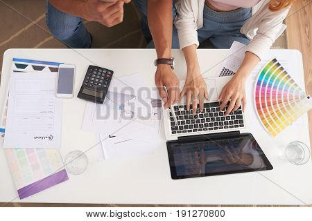 Above view of young couple planning  new house design using laptop at table with color swatches and palettes