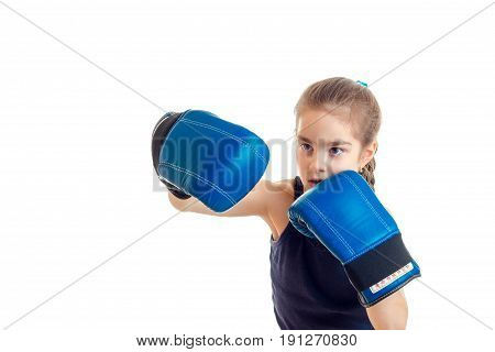 cute little girl practicing boxing in blue gloves isolated on white background