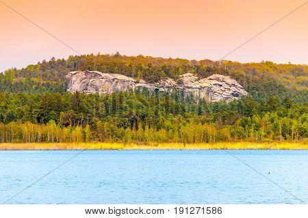 Sandstone rock formations hidden in the forest near Komarov pond, Bohemian Paradise, Czech Republic.