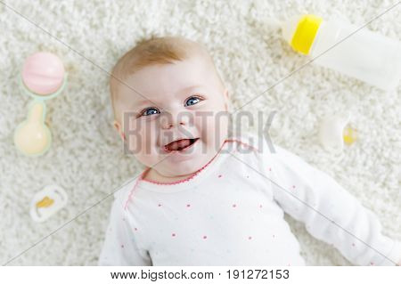 Cute adorable newborn baby playing with colorful pastel rattle toy, nursing milk bottle and dummy. New born child, little girl Family, new life, childhood, beginning concept