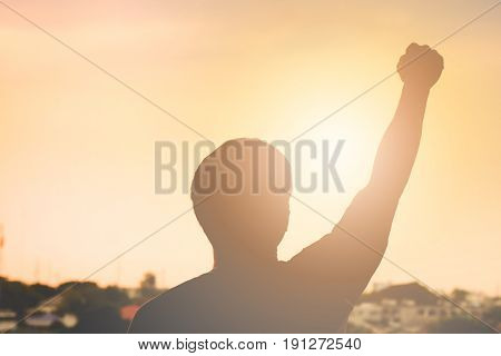 The silhouette of a handful of men as winners. Abstract background city landscape sunset