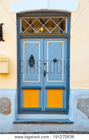 A beautiful vintage blue door with orange inserts with an old handle and a lock. The same doors you can find in historical centers of many european cities.