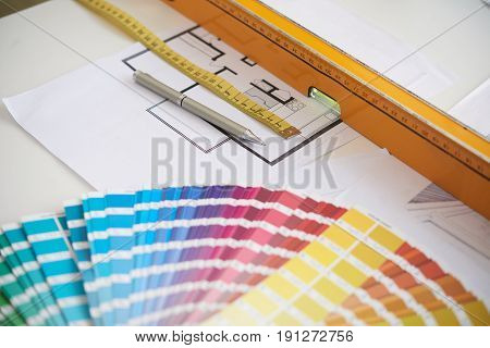 Group of objects for interior design on work  table: color swatches, floor plans and rulers, closeup background image