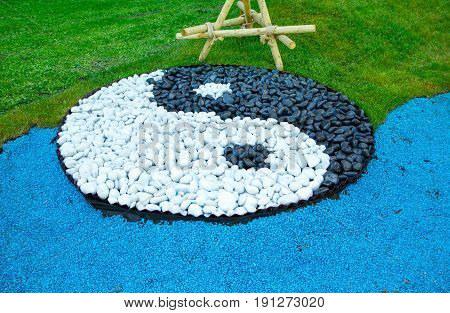 Sign of yin yang laid out of black and white stones on a green lawn