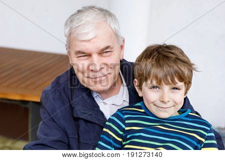 Laughing grandfather with his grandson as they play together. Happy kid boy and senior man having fun together. Generation, grandchildren, love, family
