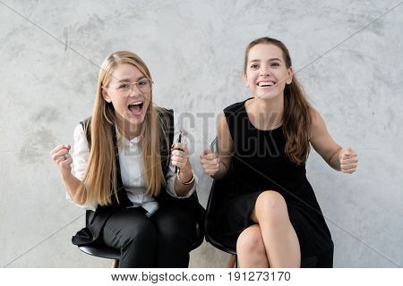 Portrait of two Caucasian smiling young girl in casual clothes celebrating victory or successful. Yes Victory Successful concept