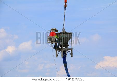 crane lifting concrete mixer container and worker in construction building commercial in site workplace
