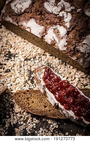 Fruity Jam on Traditional Whole Grain Rye Bread on Dark Wooden Table Background