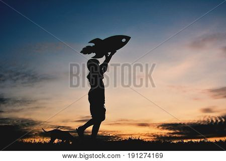 Silhouette boy holding a rocket paper and playing with little dog on the sky sunset color of vintage tone