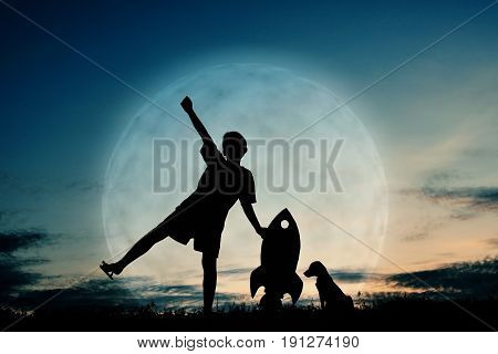 Silhouette boy holding a rocket paper and playing with little dog on the sky with moon background color of vintage tone