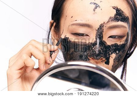 Woman takes off cosmetic mask on isolated background portrait.