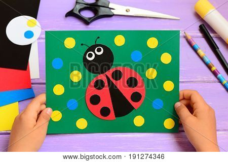 Child holds a summer card in his hands. Child made a paper ladybug card. Stationery on a wooden table. Easy paper circle crafts for teaching kids to cut and glue. Developing kids motor skills