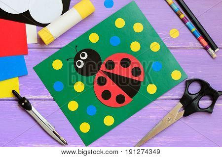 Ladybug card. Ladybug card, scissors, glue stick, pencil, marker, paper set, compass on a wooden table. Paper and glue crafts activities for kids at home, in kindergarten or summer camp. Top view