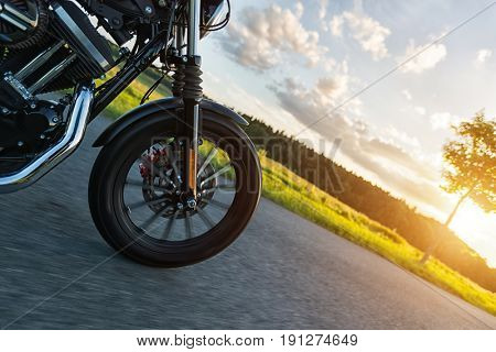 Detail of front wheel of high power motorbike in nature with beautiful sunset light. Travel and transportation. Freedom of motorbike riding