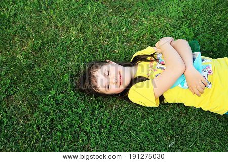 Young girl on the background of green grass