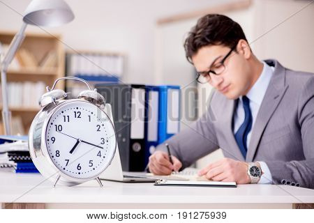 Businessman with clock failing to meet deadlines