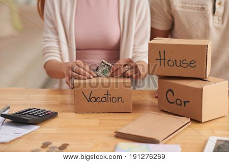 Closeup portrait of young couple putting money to piggy banks, saving  for house, car and vacation