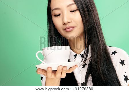 Woman holding a mug with a saucer, woman looking at a mug on a green background.