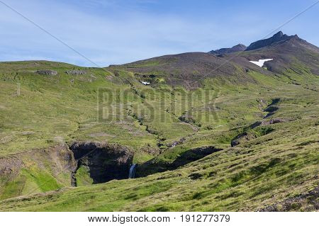 Icelandic Landscape With Green Hills Furrowed By Numerous Small Rivers And Waterfalls. Beautiful Lan