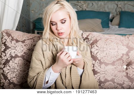 Portrait of charming girl in sweater sitting on a sofa and drinking tea or coffe.