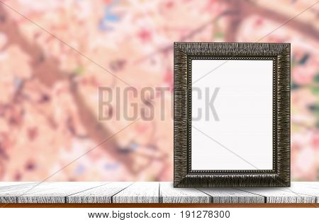 Old picture frame with blank space put on wooden table top and flower nature background use for products of pictures or texts display