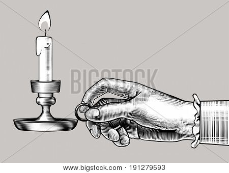 Woman's hand holding a candlestick with burning candle. Vintage engraving stylized drawing