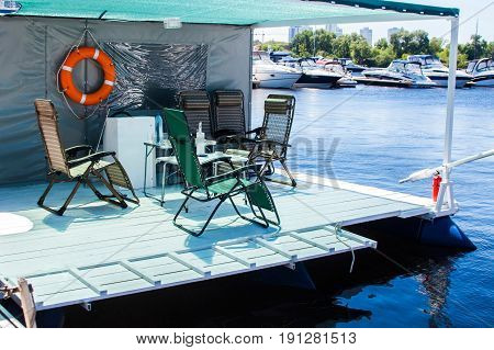 Vacation and slow lifestyle. float house good for vacation. dining table and chairs on of indoor beach terrace over water surface. Raft for rest on the water