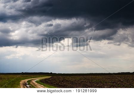 Country road disappearing into the distance on the background of storm clouds