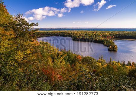 Michigan Autumn Scenic Panorama. Vibrant autumn color in the northern Michigan forest with the vast blue waters of Lake Superior in the background. Spectacle Lake overlook in Brimley, Michigan.