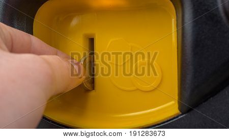 Close-up Hand putting a coin into yellow self service machine