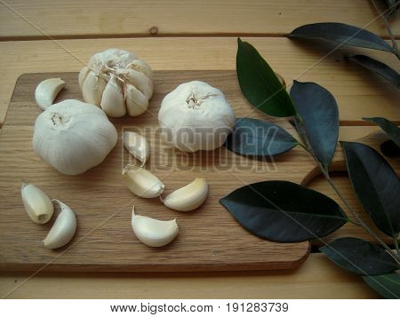 Whole garlic and slices on a cutting board and bay leaves.