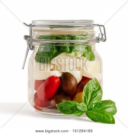 Fresh farm style layered caprese salad in an closed lid mason jar before adding dressing with basil sprig in front isolated on white.