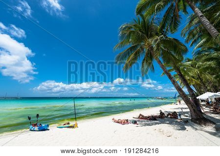 BORACAY, WESTERN VISAYAS, PHILIPPINES - MARCH 27, 2017: Wide angle view of the White Beach in a summer day with some tourists. Some of them use the coconut trees to protect the sun heat.