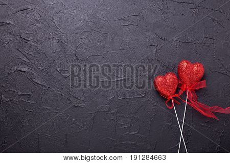 Two red hearts on textured black background. Place for text. Flat lay.