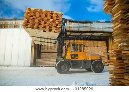 machine is lifting lumber on a wood factory.it is heavy