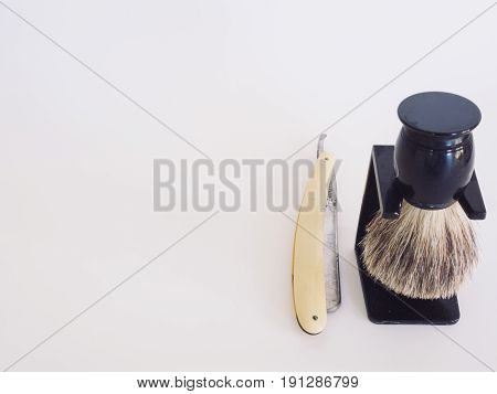 Old fashioned straight razor and badger hair brush with stand. White background. Isolated.