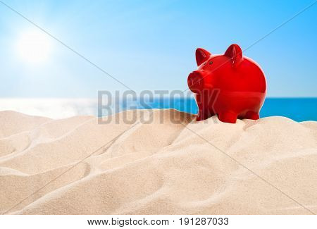 On the Beach - piggy bank on a sand dune in front of beautiful azure sea on a sunny day