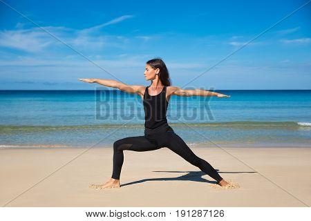 Beautiful sporty fit yogini woman practices yoga asana Virabhadrasana - warrior pose on the beach