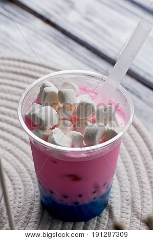 bubble tea in pink and blue color in a plastic Cup with a straw. The top is sprinkled with marshmallows.Soft, beautiful colors