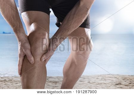 young sport man with strong athletic legs holding knee with his hands in pain after suffering muscle injury during a running workout training in Summer sea beach background with lens flare