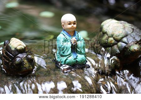 little buddha monk statue is sitting in the middle of waterfall