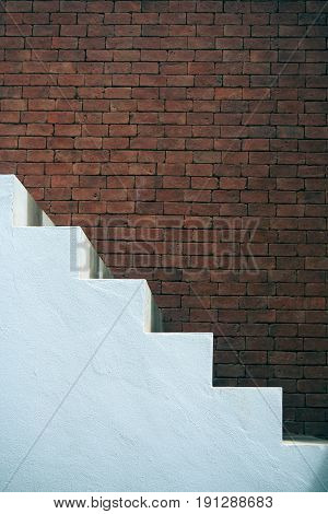 Business Success Concept : Side view of white empty stairs with brown brick wall background. (Vintage filter effect)