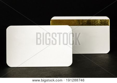 A photo of two blank white business cards with rounded corners, one of them with a golden stripe, on a black background, with a place for text
