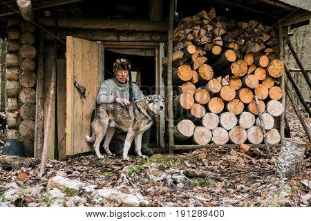 Hunter with a hunting dog at a lodge in the forest